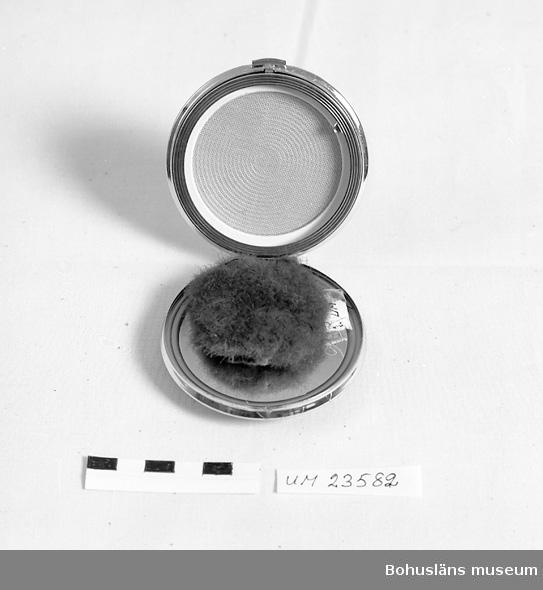 Föremålet visas i basutställlningen Kustland, Bohusläns museum., Uddevalla.  Rund puderdosa i gulmetall. Locket täckt av emaljimiterande gulmarmorerad plastskiva. Undersidan dekorerad med inpressade koncentriska cirklar. På lockets insida spegel.                                          Inlagd i skyddspåse i svart merciserad bomull.                         Ur Langes varusortiment.     Langes Parfymeri låg i början av 1900-talet på Kilbäcksgatan, sedan vid Kungsgatan 9, i samma hus som Bokströms guldsmedsaffär. Butiken flyttade 1989 till Norra Drottninggatan 8.                                                      Affären Kungsgatan 9 fotodokumenterad och med intervju med innehavaren Marianne Karlsson, se Bohusläns museums bildarkiv, UMFA53250:0001 - 0024