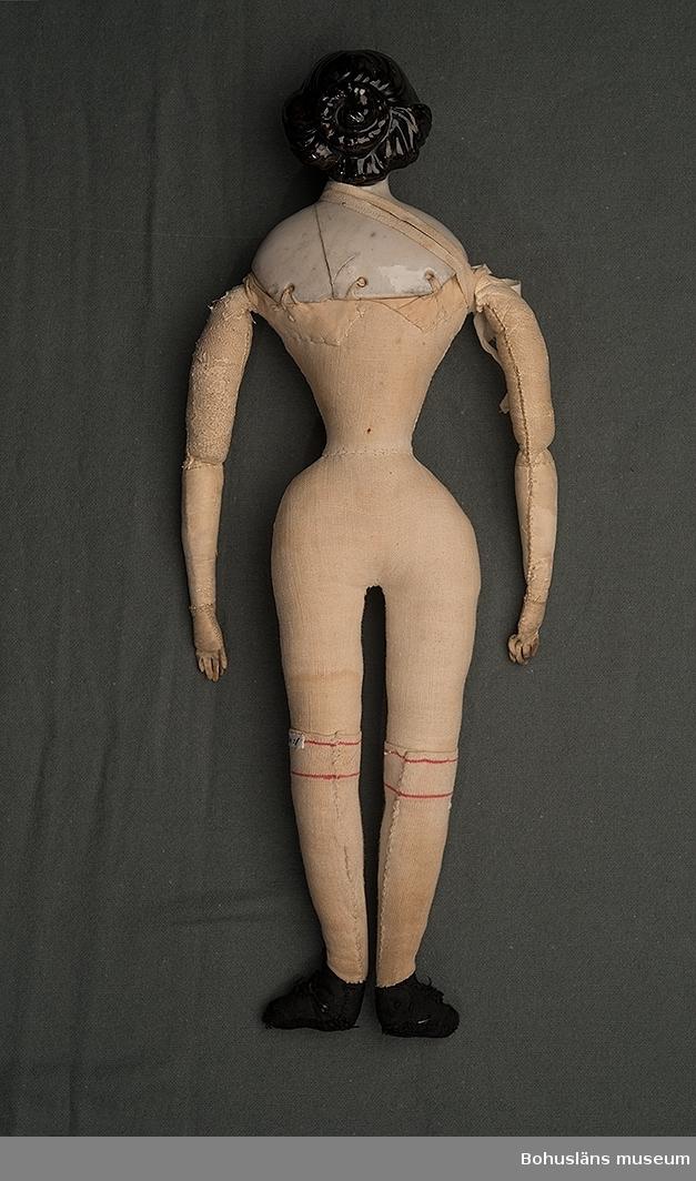 """Dockans namn är """"Adéle"""". Huvud av vitt porslin med svart hårknut i nacken. Kroppen av vitt bomullstyg stoppad. Trol. med vadd, armarna klädda med skinn. På fötterna svarta tygskor av sidenliknande tyg. Sprickor i porslinet ihoplimmade. Kroppen är hemtillverkad.  UM023864:002 - UM023864:008 är de kläder som docka UM023864:001 var klädd i vid insamlandet.  Övriga kläder till dockan, se UM023865 - UM023901. UM023864 - UM023901 har varit nedpackade så länge givaren kan minnas."""
