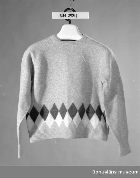 410 Mått/Vikt  ÄL:46 CM  Grå/vit/svart. Krympt. Rutmönster i nederkanten på framsidan. Tröjan tillsammans med ett par byxor (UM 24210) samt en orangefärgad anorak med dragkedja fram och kapuschong med svart pälskant + promenadskor, användes som skolkläder när givaren (född 1944) gick i skolan i  Lysekil.