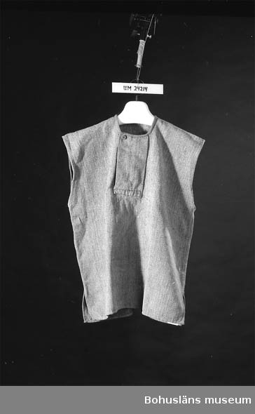 Föremålet visas i basutställningen Kustland,  Bohusläns museum, Uddevalla.  Kyprat helylle. Tyget är liksidigt. Ljus varp som gulnat och mörkgrått inslag. Saknar ärmar, ärmhålen fållade med kaststygn. Öppnas med ett sprund mitt fram (vikt lucka) och knäpps med knapp. Halsringningen fållad med ett smalrandigt bomullsband. Se UM016648 (Handkläde), UM024215 - UM024218. Bussarongen hittades vid en bouppteckning efter Vivis mor, död 1982. Modern bodde i Lysekil, men härstammade från Tjörn (Apelröd, Valla socken). Föremålet är troligen använt på 1900-talets början.