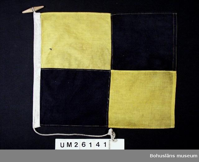 """Två svarta, gula fält diagonalt ställda.  Betyder: """"Stoppa farten ögonblickligen"""". Användning; se UM026139  Personuppgifter se UM026024"""