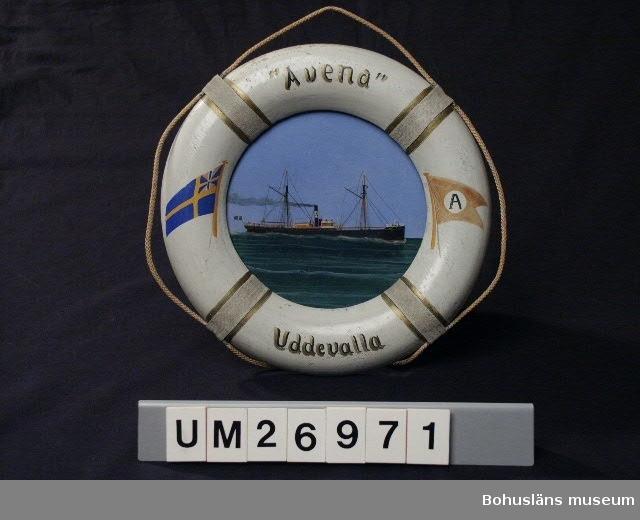 """Föremålet visas i basutställningen Uddevalla genom tiderna, Bohusläns museum, Uddevalla.  Tavla av en ångskonerten s/s Avena med ram i form av en livboj. Målningen är gjord på papp.  Svart skrov med röda detaljer, två master samt skorsten som det kommer rök ur. Ovanför båten ljusblå himmel och under den ett mörkt blågrönt hav med ljusare vågstreck. Ramen av trä är målad i en nu mycket ljust grå nyans (från början vit?) och på fyra ställen finns dekoration av påklistrat bomullsband i samma färg med guldränder bredvid. Under bomullsbanden är en snodd trädd så att den ligger i lösa bågar runt hela ramen. Allt för att efterlikna en livboj. Upptill på ramen står: """"Avena"""", nertill Uddevalla, målat i guldfärg och svart. På högra sidan finns en målad bild av rederiets flagga, röd (nu brunröd) med en vit cirkel i mitten där det står A. På vänstra sidan finns en bild av Sveriges handelsflagga, en tvärskuren svensk flagga som i övre inre fältet har unionsmärke använt 1844 - 1905 från unionen mellan Sverige och Norge. Datering till innan 1905 är gjord utifrån detta. Den angivna märkningen finns på tavlans baksida, skriven med bläck.  1823 flyttade skotske affärsmannen William Thorburn till Uddevalla. Han lade grunden till ett familjeföretag som under ett och ett halvt sekel  hade största betydelse för Uddevallas ekonomi. William Thorburn tog fasta på den engelska efterfrågan på havre till alla de hästar som drog Londons cabs och landsvägsdiligenser. Firman Thorburn och söner köpte upp havre från bönderna i Bohuslän, Västergötland och Dalsland. Jordbruket inriktades alltmer på havreodling.   1874 startade William Thorburn ångbåtsförbildelse Uddevalla - London under namnet Ångbåtsaktiebolaget Avena. Avena är det första ordet i latinets beteckning på havre.   De ingående fartygen i  Ångbåtsaktiebolaget Avena var S/S Avena, S/S Sitona, S/S Annona och S/S Pollux.   Järnångaren Avena gjorde snabba resor över Nordsjön och kallades """"The North Sea Greyhound"""". Hon gick från Uddevalla sön"""
