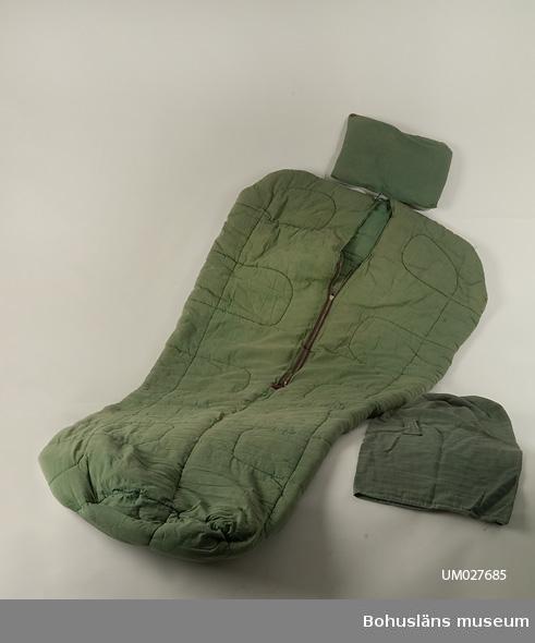 Grön sovsäck. Vaddstickat i stora rutor. 75 cm bred upptill, avsmalnande neråt till 53 cm. Metalldragkedja som stänges inifrån, nertill förstärkt med en läderbit. Fasthängande rektangulär stoppad kudde.  Till sovsäcken hör en säck av grönt tyg med påsytt handtag.  För ytterligare upplysningar om  insamlingen, utställningen 2001 och litteratur, se UM27670.