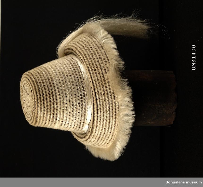 Beige toppig solhatt prydd med fransar och tofs i nylon. Använd på 1960-talet av givarens kusin, Elisabeth Madgård (f. 1950).  Föremålet har använts av familjen Abrahamson i deras sommarstuga i Sundsandvik, byggd 1939. För ytterligare upplysningar om förvärvet, se UM031385.