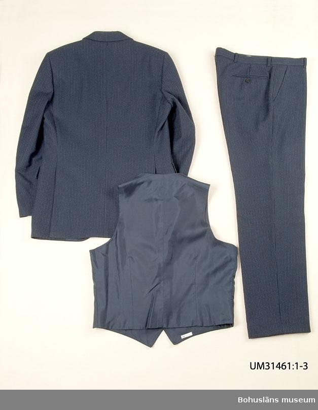 """Mörkblå kostymväst (UM031461:003) sammanhörande med kostymbyxa (UM031461:002) och kostymkavaj(UM031461:001).  Mörkblå ull med smala kritstreck i framstyckena som är skurna i varsin snibb.  Bakstycke i dubblerat fodertyg av mörkblå satin. Framstyckena fodrade med mörkblått satintyg. Enkelknäppt med sex svarta knappar. I en sidsöm inuti fästat en firmaetikett med texten:  """"TIGER OF SWEDEN STORL. SIZE. GRÖSSE  B 48. 451 26 UDDEVALLA"""