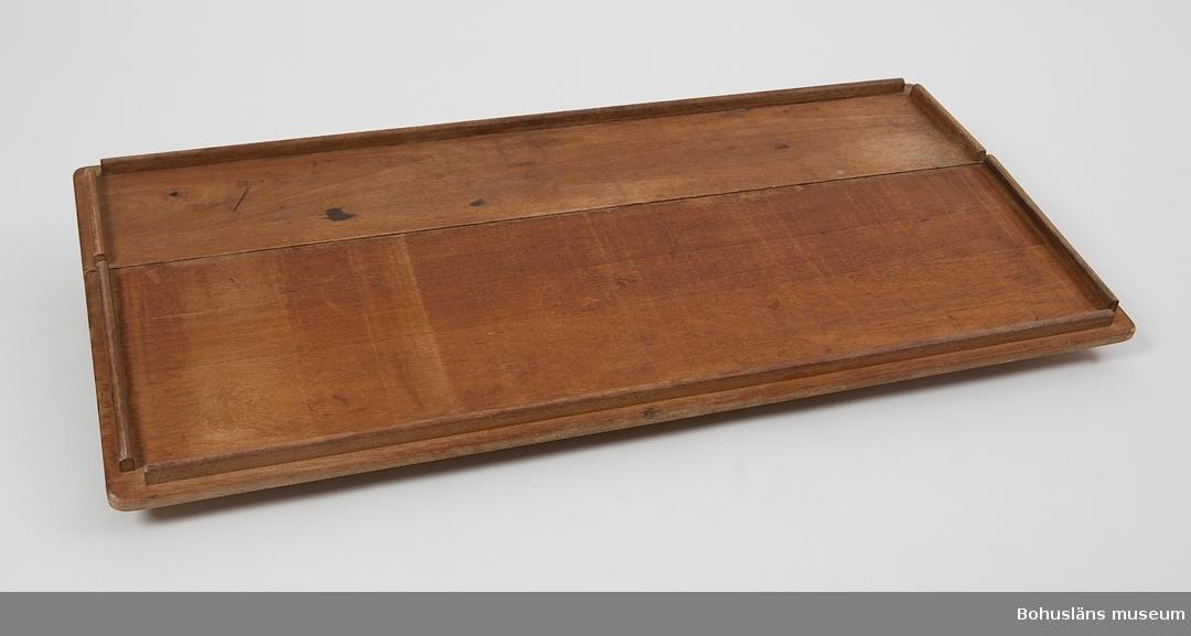 Teakbord med två uppfällbara långsidor. Den ena klaffen är 29 cm bred, den andra 19 cm bred.  Sidostyckena fästade i pianogångjärn av mässing. Längs bordkanterna löper en list som fungerar som slingerställ. Mässingsskruvar.  Undertill två mässingshållare där två bordsben placeras. Benen placeras i hål i durken.