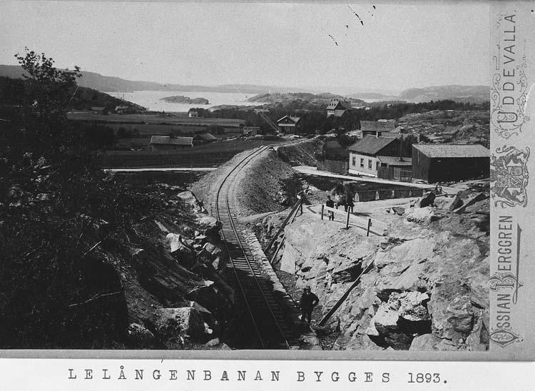 """Tryckt på kortet: """"Lelångebanan bygges 1893"""". Enl. tidigare noteringar: """"Vy mot väster i Uddevalla, Lelångenbanans byggande år 1893""""."""
