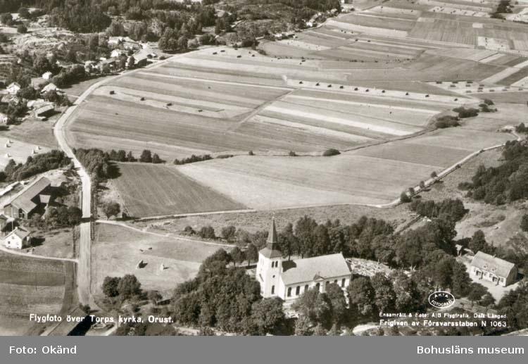 """Tryckt text på kortet: """"Flygfoto över Torps kyrka, Orust."""" """"Ensamrätt & Foto: A/B Flygtrafik, Dals Långed."""""""