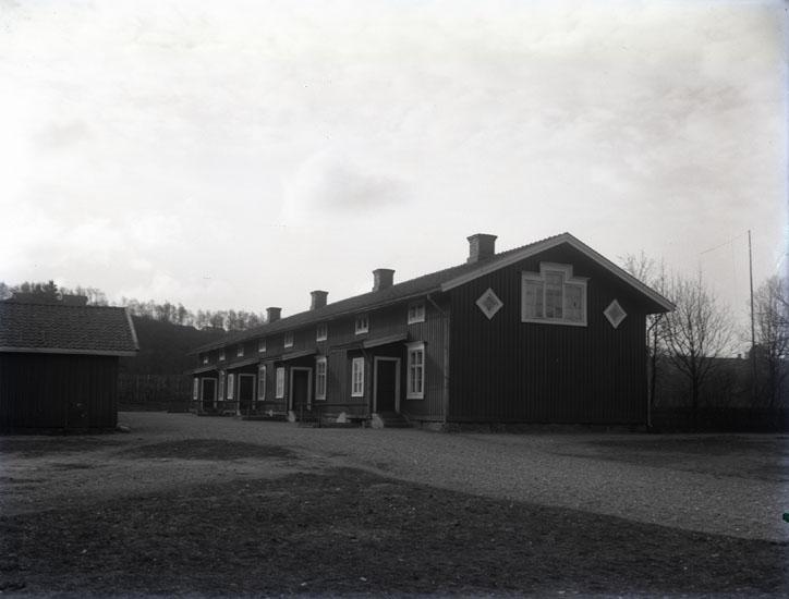 """""""1930. 24. Baracken arbetarbostad vid Munkedals fabrik.""""  """"Huset innehöll åtta bostäder. Huset revs på 1960-talet. Vedbod till vänster."""""""