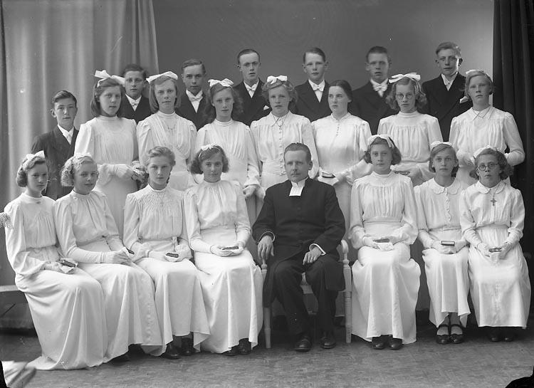 """Enligt fotografens journal nr 6 1930-1943: """"Ödsmåls Konfirmander"""". Enligt fotografens notering: """"Kyrkoherde Norén Ödsmåls konfirmander Stenungsund. D. 26/5 1942""""."""