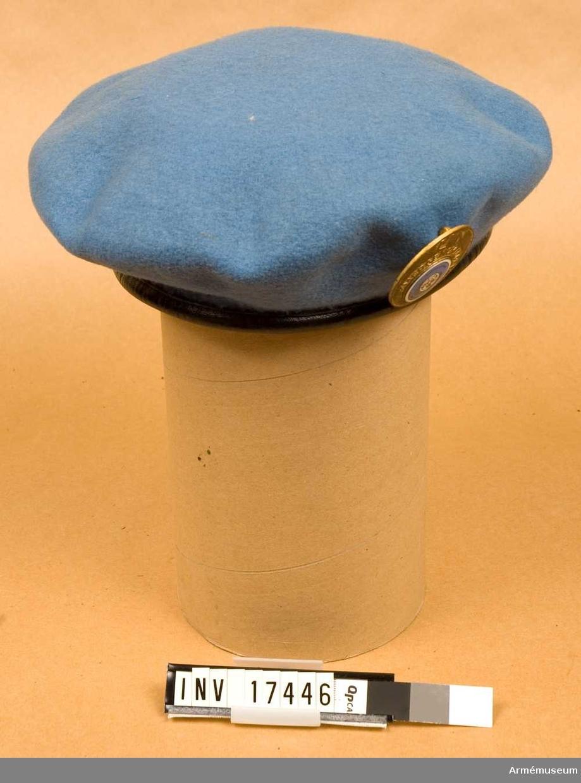"""Grupp C I. Basker för trupp ur Förenta Nationernas övervakningskommission vid Suez och Gaza-remsan i Egypten 1956-67. Av ljusblått kläde med svart kant (svettrem) av skinn. På vänstra sidan ett emblem av emaljerad gulmetall med text: """"UN EMERGENCY FORGE United Nations Nations Unies"""". Foder av svart bomullstyg med märkning: """"Fleur de Lis BERET 6 7/8  Dorothea Knitting Mills LIMITED TORONTO"""". Beskrivning 1973 S W-ge."""
