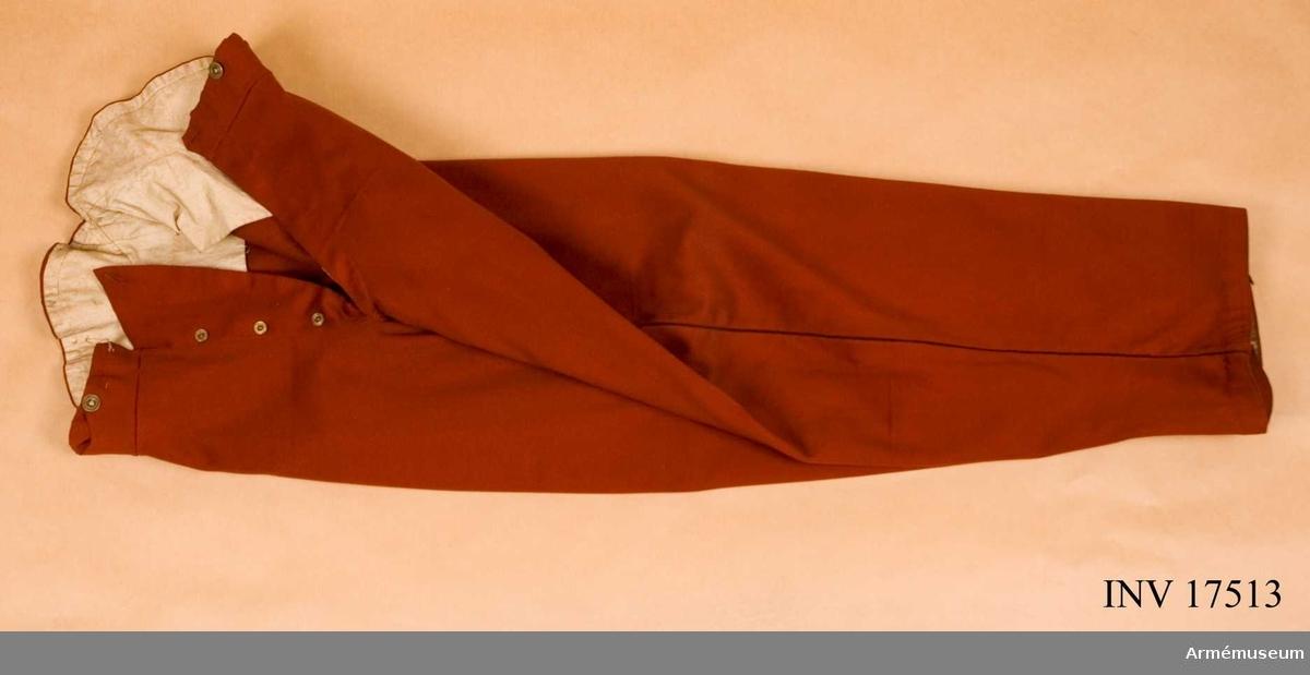 """Grupp C I. Byxor (pantalon d' ordonannance) av rött kläde och har två sidofickor och på framsidan (för klocka). Knapparna är av mässing:tre för sprundet och sex för hängslen. PÅ båda ytt- sidorna finns det svartblått passepoal. Fodertyget är vitt. På byxbenens nedre (baksidan) finns fyra små knappar. Litteratur. Enligt Arméenalbum II Leipzig. Die Französische Armée, sid 29 Die Beinekleider. Byxor för ridande trupper är röda med svart blå passepoal. Uniformenkunde, Kötel-Sieg, Hamburg 1937 sid 170. År 1823 infördes i Kavalleriet  byxor av krapprött kläde. Collection  compléte des tracés de coupe des Effets d'Habittement. Ministére de la Guerre , 1845-47, plansch 22 ritning av """"pantalon d' ordonnance"""" för Kavalleri."""