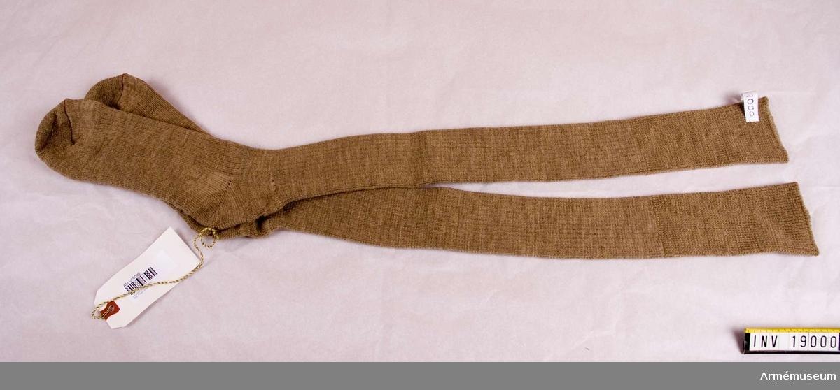 Knästrumpor m/1961, Tropikuniform.Stickade strumpor av beigefärgat yllegan. Mudd upptill att  vikas ned under knäet. Storlek 11. Strumporna är ribbstickade i skaftet och frottéstickade i foten.