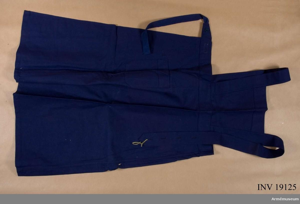 """Samhörande  nr: 19118-27. Av marinblå s k bomullstvills. Det har bröstlapp, ficka på höger sida. Reglerbara hängslen. På linningens insida """"Tre kronor"""" och bokstäverna J.F.B. påstämplade och bredvid två vävda, vita band med text i blått: """"I 3 kök"""" och i rött: """"C 46"""" =storlek. Knyts i midjan med kypertvävda bomullsband. Oanvänt."""