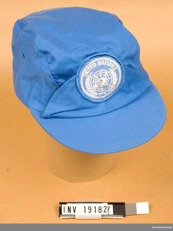 Storlek 60. Av blått bomullstyg. Fasonerad efter huvudformen och med uppslag och FN-emblem 1980 mitt fram. Mössan har en styv, överklädd skärm i samma tyg som för övrigt. Invändigt stämplad med kronmärket, 1981 och Hestra Reklam AB.