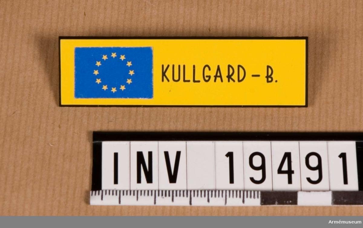 Namnskylt avsedd att fästas på klädedräkten. Den är tillverkad i ett plastmaterial, försedd med namnet KULLGARD B. och symbolen för europa dvs 12 gula stjärnor i ring på blå botten. På baksidan en fästningsanordning.  Samhörande nr AM.19483-19494