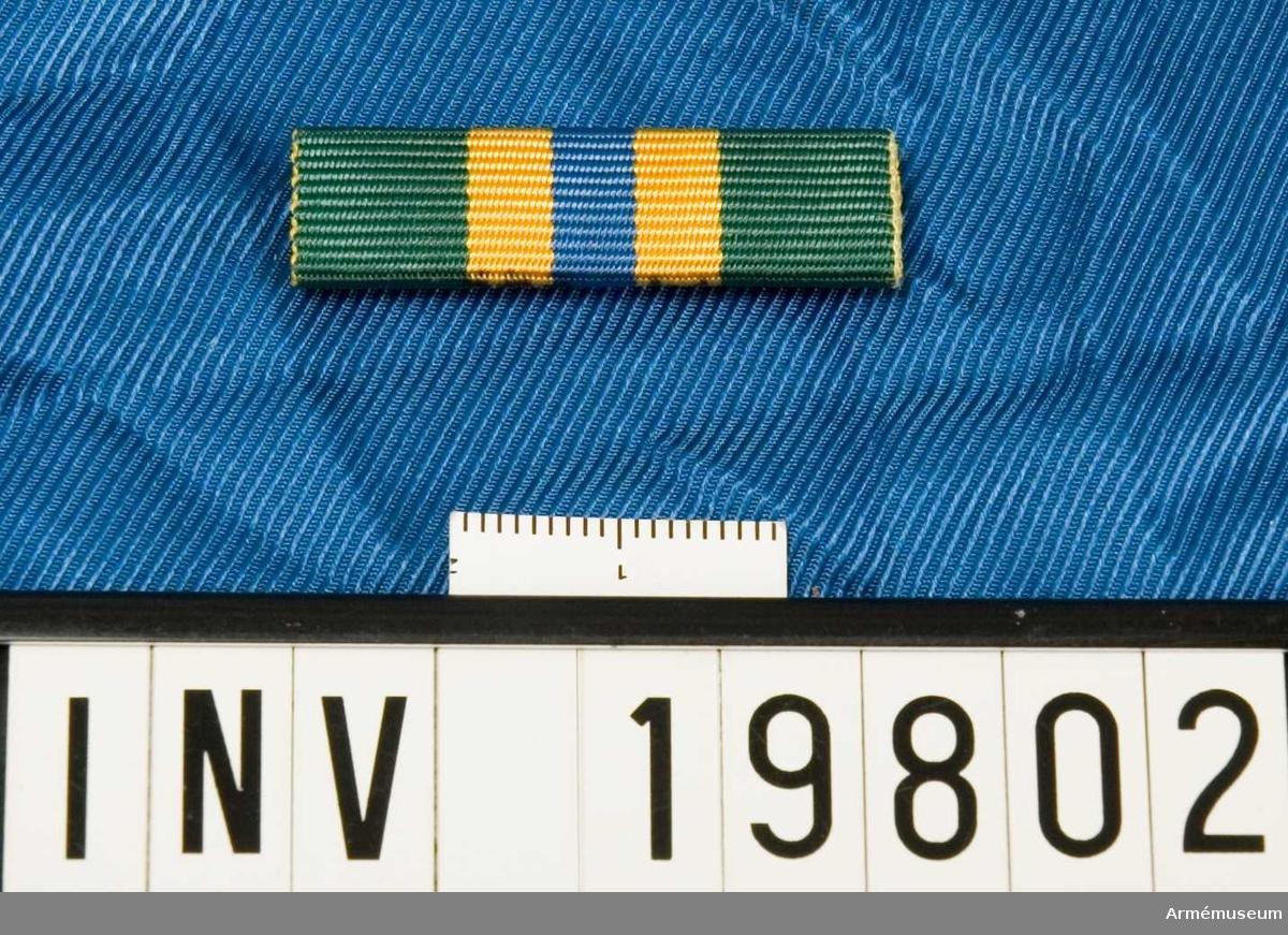 Grönt band med en blå rand i mitten åtföljd av en gul rand på vardera sidan. Släpspännet förvaras i ask tillsammans med en medalj och en miniatyrmedalj.
