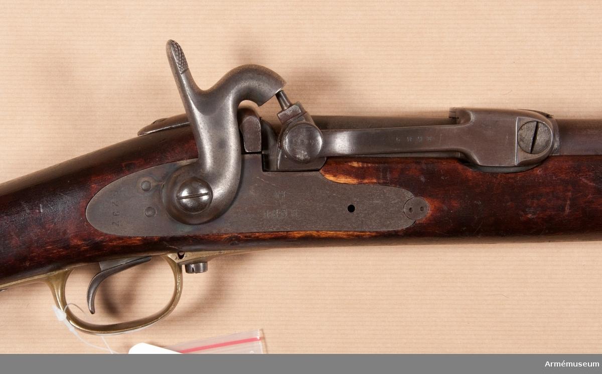 """Grupp E II e.  Vapnet är ursprungligen ett mynningsladdningsgevär m/1860 (se A. M.1932:4554) som ändrats till kammarladdare och med undantag av kammarladdningsmekanismen, överenstämmer geväret helt med 1860 års modell.  Antalet räfflor är fyra. Räffelstigningen är ett varv på 112,8 cm. Spetskulan: l:23,2 mm, d:12,32 mm, vikt: 24,9 g. Krutladdningens vikt: 6,38 g. Loppets rel. längd är 71 kaliber.  Pipan är brungjord. Baktill är en gråhärdad, 2,1 cm.lång mutter påskruvad på pipan. Denna """"tappmutter"""" har på var sida i jämnhöjd med loppets överkant en kraftig tapp. Vinkelklaffsiktet, av 1860 års modell, sitter 6,9 cm framför tappmutterns framkant. På undersidan omkring 1 cm. framför tappmuttern är ett kraftigt häfte fastlött vid pipan. Kornet är som på m/1860. Baktill på pipans översida står krönt C, LRN och C.F. På vänstra sidan av pipan och tappmuttern är numret 1311 inslaget. På undersidan finnes P, 2, AF och 1864.  Kammarladdningsmekanismen har ej låda, vilken i stället ersättes av ett 18 cm. långt, 1,9 cm. brett och 0,4 cm. tjockt svagt rännformigt bottenjärn. Bottenjärnet har framtill ett avlångt hål, i vilket piphäftet införes. Bottenjärnet fasthålles vid pipan genom en bult, som går genom stocken och genom ett hål på häftet nedaför bottenjärnet. Baktill är bottenjärnet medelst en underifrån, från varbygelns främre arm kommande skruv fäst vid det vinkelformiga svansjärnet. En kraftig bladfjäder är med en skruv fäst vid bottenjärnets undersida 6,6 cm bakom framänden. Fjäderns långa bågböjda bakre arm går upp genom ett rektangulärt, 2,3 cm, framför bottenjärnets bakände befintigt hål. Den korta nedböjda främre armen tjänstgör som laddstocksfjäder. Svansjärnets stjärt är infälld i kolvhalsens översida och fasthålles av den nedifrån isatta korsskruven. På bottenjärnets undersida står siffran 1, på översidan 1311. Sistnämnda nummer finnes även å svansjärnsstjärtens undersida, men på stjärtens högra sida ett B. Kammartycket liknar fullkomligt det å 1864 års kammarladd"""