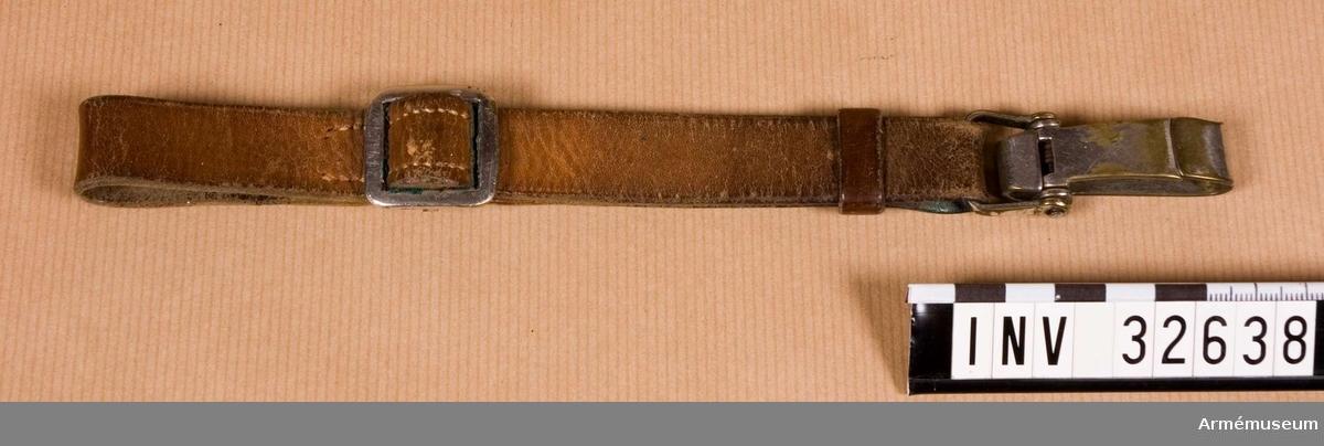 Grupp C I Ur uniform m/1923: vapenrock, ridbyxor, sporrar, portepé, sabel, livrem, sabelrem. Livgardet till häst K 1. Sitter på livremmen.   Samhörande nr AM.32631-8