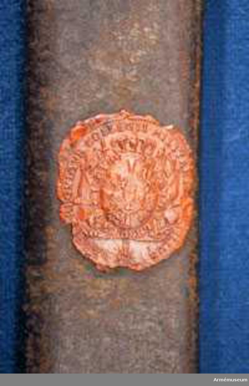 Grupp D II.  Baljan är av brunt sulläder samt har munbleck och släpsko av mässing. Munblecket har koppelhake och längs dess överkan går på insidan en ingraverad rand, men på utsidan två liknande, horisotala ränder. Släpskon har slitskena av stål och fasonerad överkant. En bit från överkanten går på insidan en, men på insidan två ingraverade ränder lite snett över släpskon.På koppelhaken är siffran 6 inslagen och baljans utsida finns Krigskollegiums sigill i rött lack.J Alm 1952.