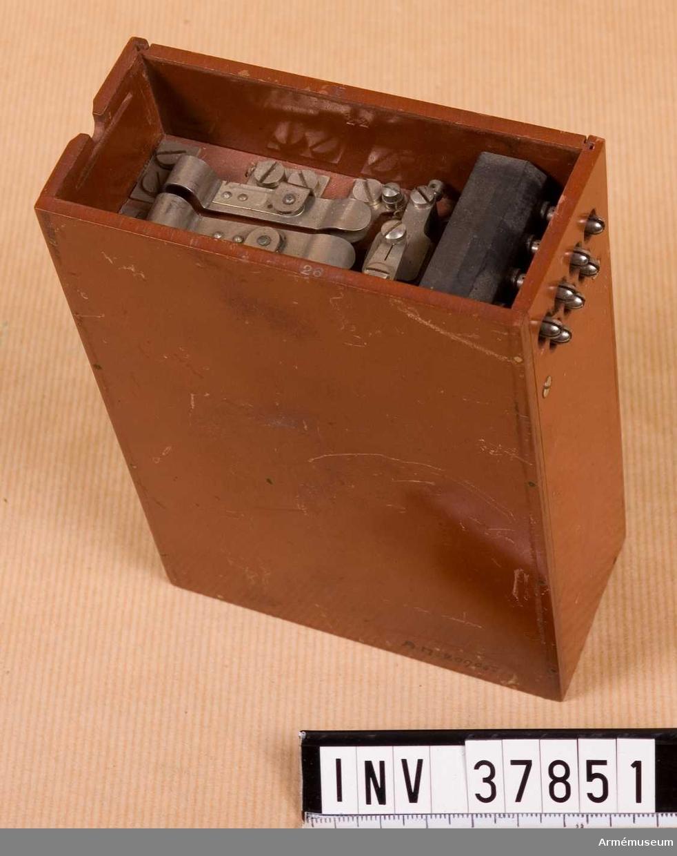 Grupp H I.  Fiberlåda med innehåll. Utan hörnbeslag. Saknas: lådans lock med tillhöriga delar, batteri, induktionsrulle.