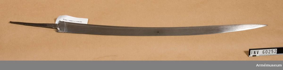 """Grupp D II. klingans bredd upptill är 34 mm. Klingan är krökt och har längs  ryggen en blodrand. Till större delen av sin längd är den  eneggad, men 165 mm ovanför udden får den egg även på ryggsidan.  I klingans övre del finns ett hål, genom vilket ett snöre går. I  snöret sitter en skadad pappersbit, på vilken  Generalfälttygmästareämbetets största sigill i rött lack finns,  samt påskriften """"Huggare - Klinga .............. för afslipning  utaf äldre ......gare -  Klingor.Stockh......""""."""