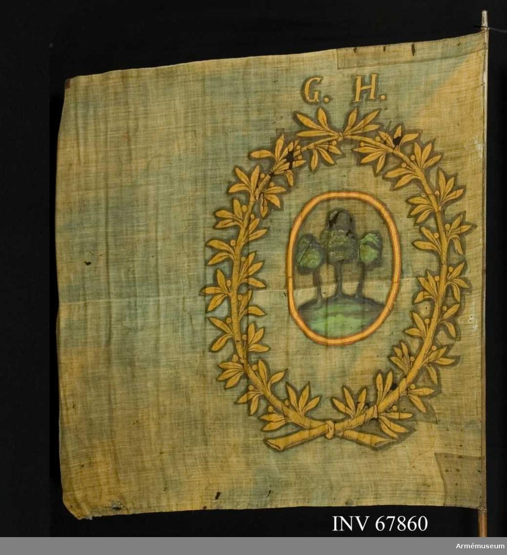 Duk: Tillverkad av enkel blå linnelärft. Duken fäst vid stången med järnspik på en skinnremsa.   Dekor:  Målat omvänt lika på båda sidor. En oval röd och guldkantad sköld med tre träd (enbuskar), bruna stammar och gröna kronor på grön mark. Skölden omges av en krans av två lagerkvistarmed blad och bär i gult, nedtill och upptill hopknutna. Över kransen: G.H.  Stång, brun.
