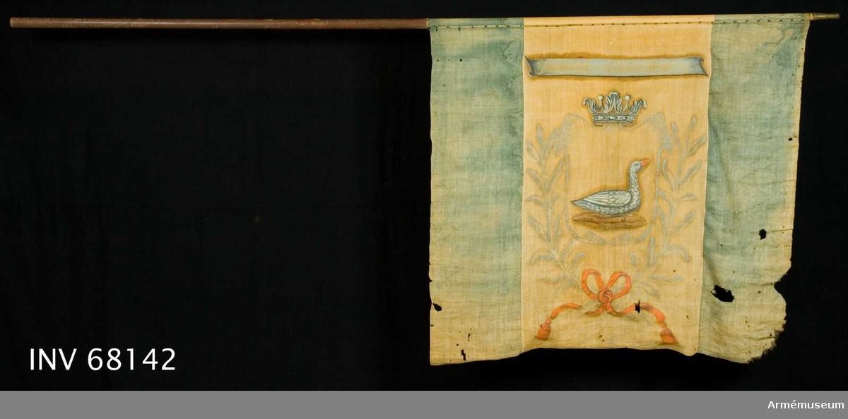 Duk: Tillverkad av enkel gul och blå linnelärft. Sydd i tre våder: blå, gul och blå. De blå vådernas stad vända åt ytterkanten. De blå fälten är också tunnare vävda än de gula. Fäst med en rad tännlikor på ett vitt, kypertvävt band.   Dekor: Målad omvänt lika på båda sidor på det det gula fältet. I den med öppna kronan krönta skölden finns en gås med orangeröd näbb.  Skölden innefattad av två kvistar, sammanbundna nedtill i rosett. Bandet i orangerött med långa tofsprydda ändar. Över det hela finns ett grått språkband, med text i gult.   Stång: Tillverkad av brunmålat trä. Saknar spets. Holk av förgylld mässing.