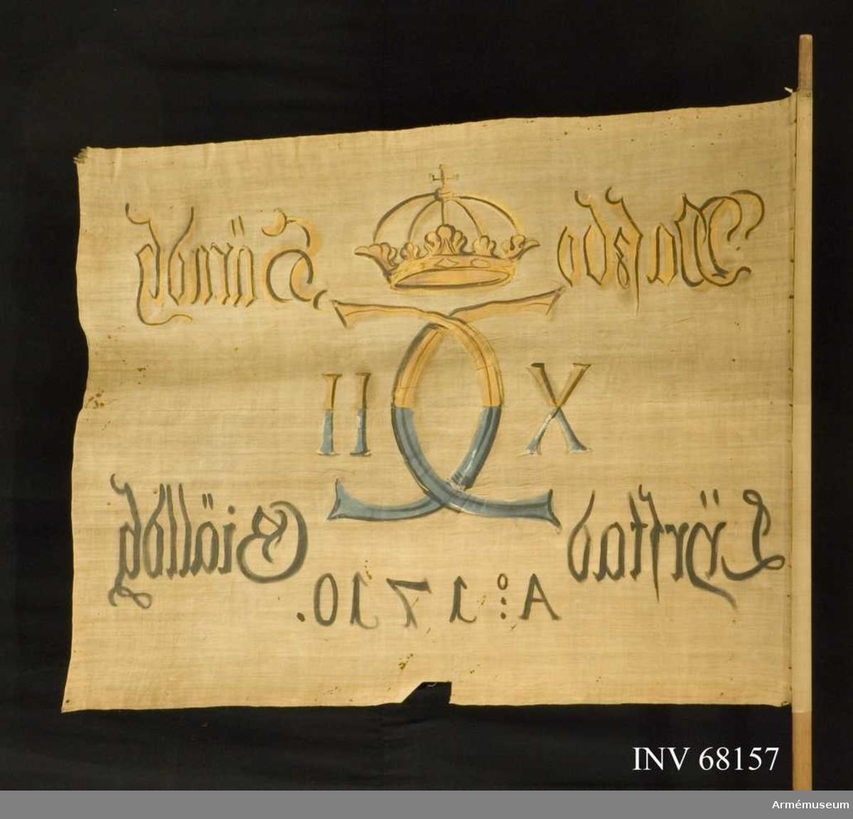 Duk av enkel vit linnelärft, sydd av två horisontella våder. Fäst med en rad mindre järnnagel på en läderremsa.  Dekor: Målad, endast på dukens insida, i mitten Karl XII:s namnchiffer, dubbelt C, med X -II, på ömse sidor. Krönt med sluten krona, i gult och brunt på den övre våden, i blått och svart på den nedre. Text på ömse sidor om chiffret, upptill i gult och brunt, nedtill i svart. Under chiffret text i svart.  Stång: Tillverkad av furu.