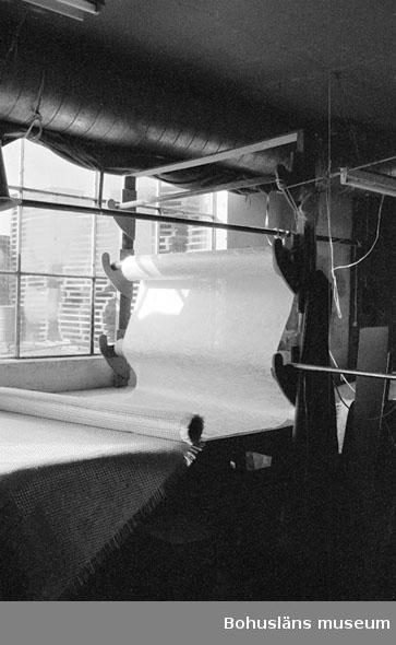 """Motivbeskrivning: """"Rolf Nicanders Båtbyggeri AB, Marstrand. Interiör från plasningsverkstaden. Glasfibermatta på uppskärningband."""" Datum: 19801003"""