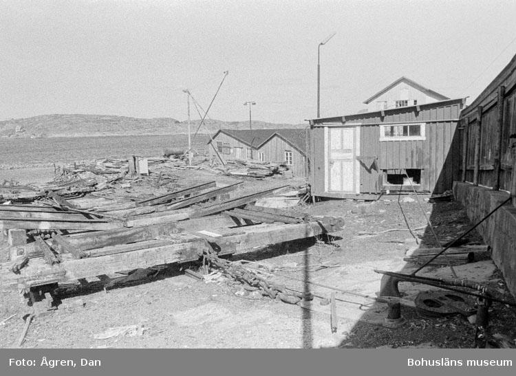 """Motivbeskrivning: """"Bergs varv på Hälsö, draganordning för slip och maskinhus mot N."""" Datum: 19800424"""