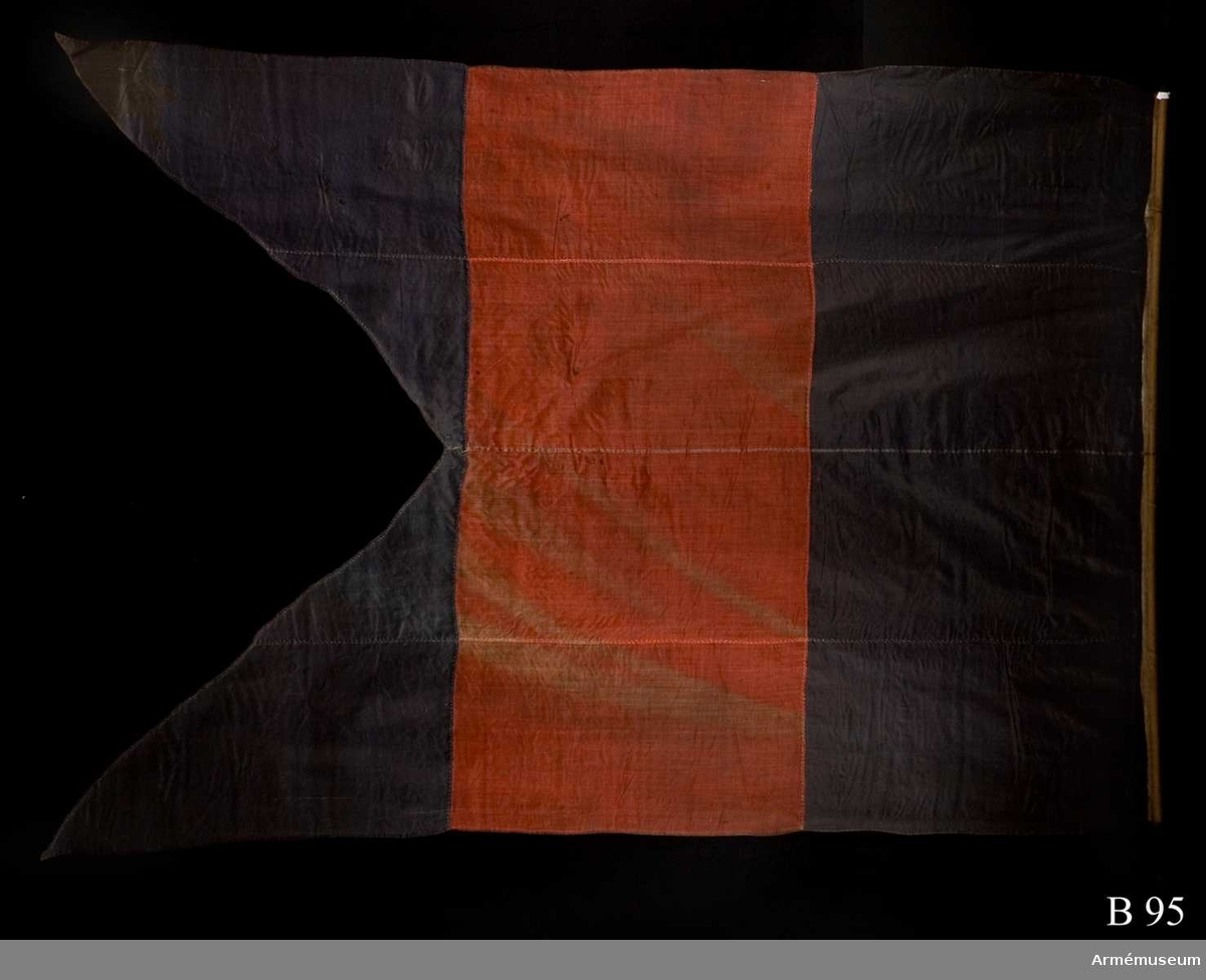 """Blå, röd och blå gös med stjärtar. Lik av vitt linne. På flaggan var tidigare fastsydd en etikett av pergament med texten: """"Denna ryska gös, 4 duk, är tagen uti bataillen vid Svenskund under Hans Kungl Majts egit höga befäl och anförande den 9 julij år 1790. No 5 signalflagg"""". Etiketten är borttagen vid konservering och förvaras nu i Trofésamlingens arkiv."""