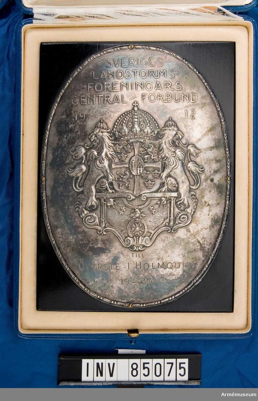 Plakett fastsatt på svart ram med inskription I blå ask med inskription på utsidan: MED VÖRDSMT TACK FÖR FÖRTJÄNSTFULLT ARBETE SOM ORDFÖRANDE ÅREN 1928-1934 FRÅN NORRBOTTENS LANDSTORMS FÖRBUND.