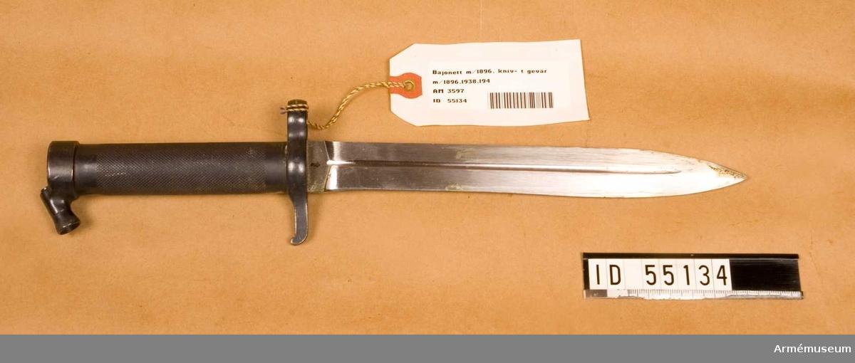 Helt tillverkad av stål med rörformigt lättrat grepp med konisk låsknapp och pipring. Rak, eneggad klinga med smal blodskåra på båda sidor. Klingans bredd vid fästet: 25 mm. Pipringens id: 15,5 mm., tillv.nr: 895.