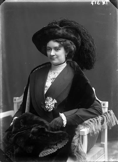 """Enligt senare noteringar: """"Ateljéfoto av kvinna, klädd i fin dräkt med pälsklädd hatt med plymer, boa och muff."""""""