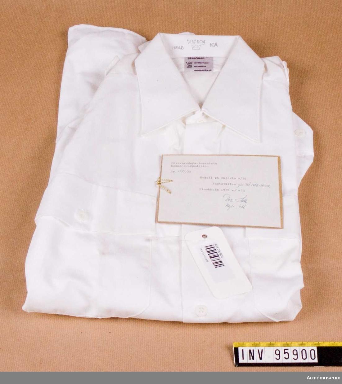 """Vit skjorta med hel, fast krage och ok av dubbelt tyg. Skjortan har bröstfickor med lock som knäpps. Fasta axelklaffar, bredd 42-45 mm, utan axelklaffshylsor. Skjortan är avsedd för alla uniformsdräkter inom försvaret där vit skjorta är tillåten. Vidhängande etikett: """"Försvarsdepartementets kommandoexpedition. Nr 1771/78. Modell på Skjorta m/78. Fastställes gm RÄ 1978-1102. Stockholm 1978-11-03 (oläslig underskrift)"""" På baksidan lackstämpel från Försvarets Materielverk."""