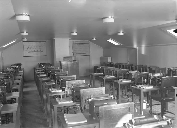 """Text till bilden:""""Skolsal med bord och skrivmaskiner i fyra lång rader""""."""
