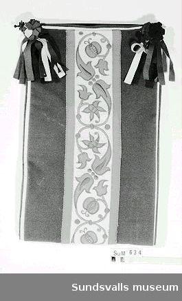 Tidningshållare i broderat kläde. Broderiet i kedjesöm och plattsöm föreställer växtslingor. Hållaren är upphängd på en svartmålad trästav. Enligt uppgift skall tidningshållaren vara sydd av givaren Agda Sundberg (född Berggren), till hennes fästman doktor Lars Sundberg under 1890-talet.