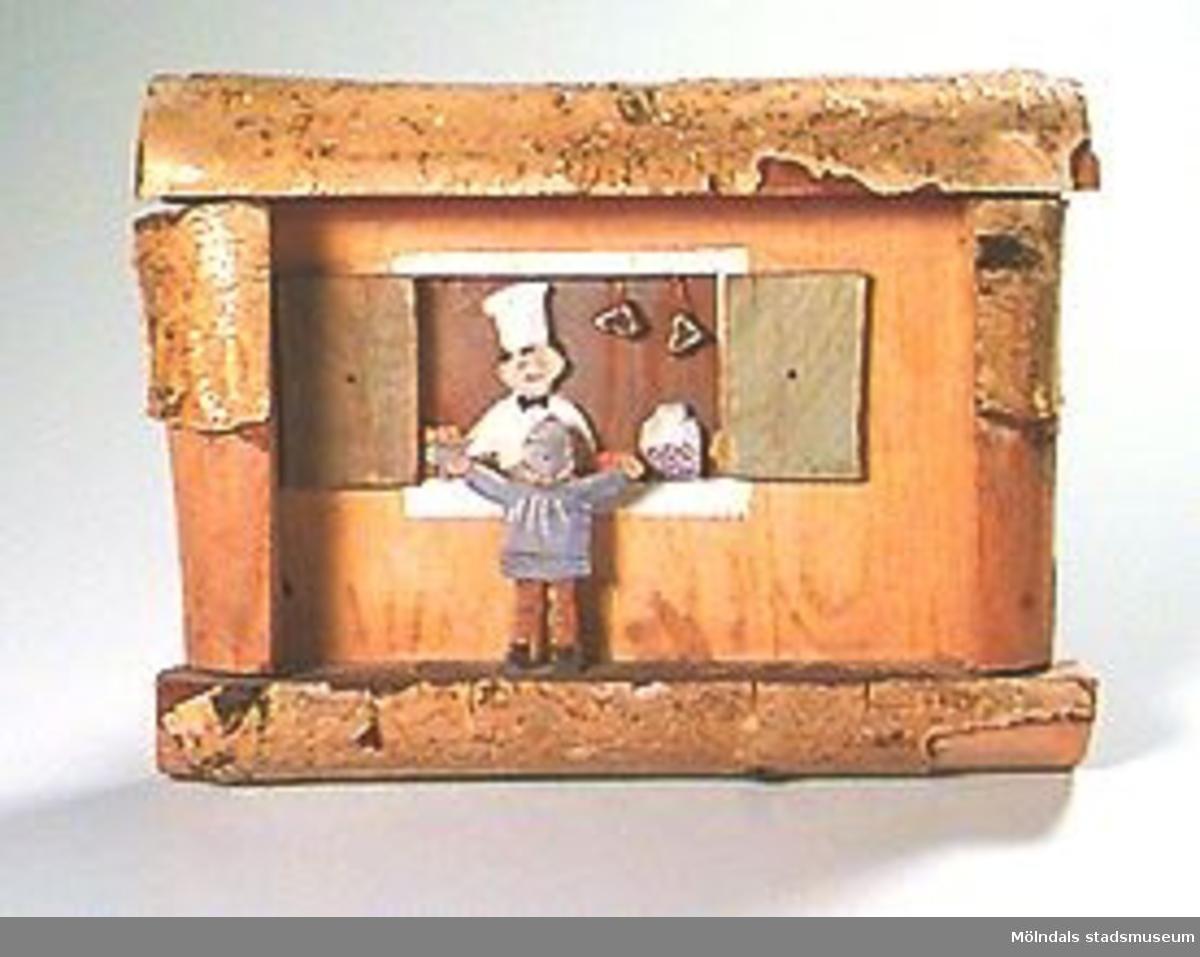 Utsågade figurer i trä. Motiv: pojke vid bageri. Som ram användes björkvedsbitar med fastsittande bark.Tjocklek: 38 mm.
