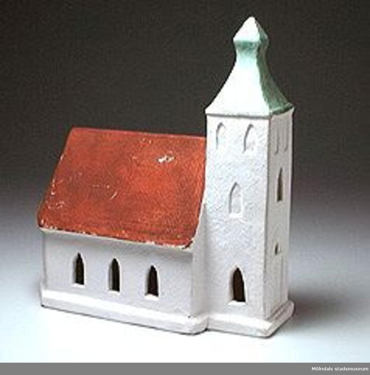 Vit kyrka med torn. Torntaket målat i grönt, kyrktaket tegelrött.