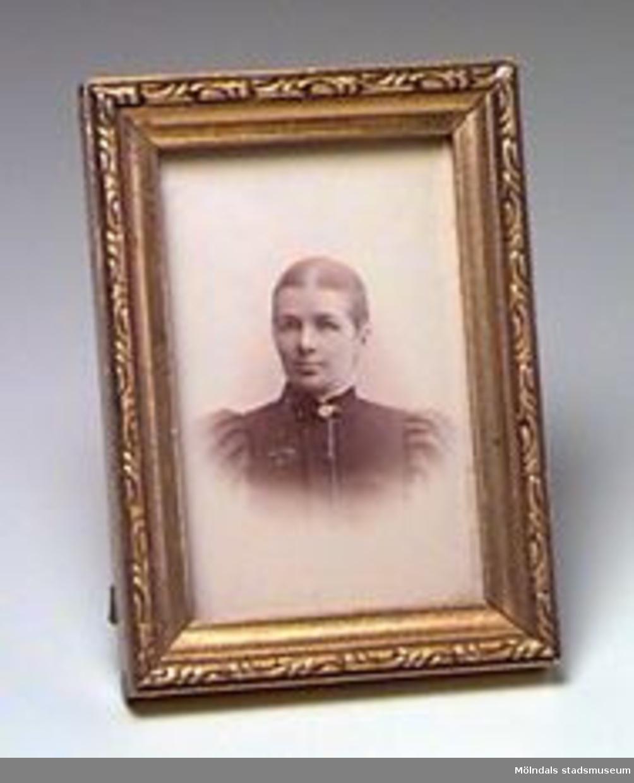 Porträttfotografi med förgylld träram. Ramen har måtten; H: 106 mm B: 76 Tj: 14 mm.Avporträtterad person är Josefina K Eriksson, Våmmedal.Tidigare sakord: porträttfoto med ram.