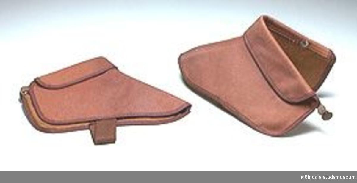 """Ett par små damasker av kraftigt brunt tyg. Resårhälla, som skall gå under """"hålfoten"""" på skon, håller damasken på plats. Resårband fästad. Tryckknapp knäpptes bak, ovan hälen. (Den bruna färgen och det grova tyget tyder på  en uniforms-damask eller sport-damask t.ex för ridning eller skidåkning.)"""