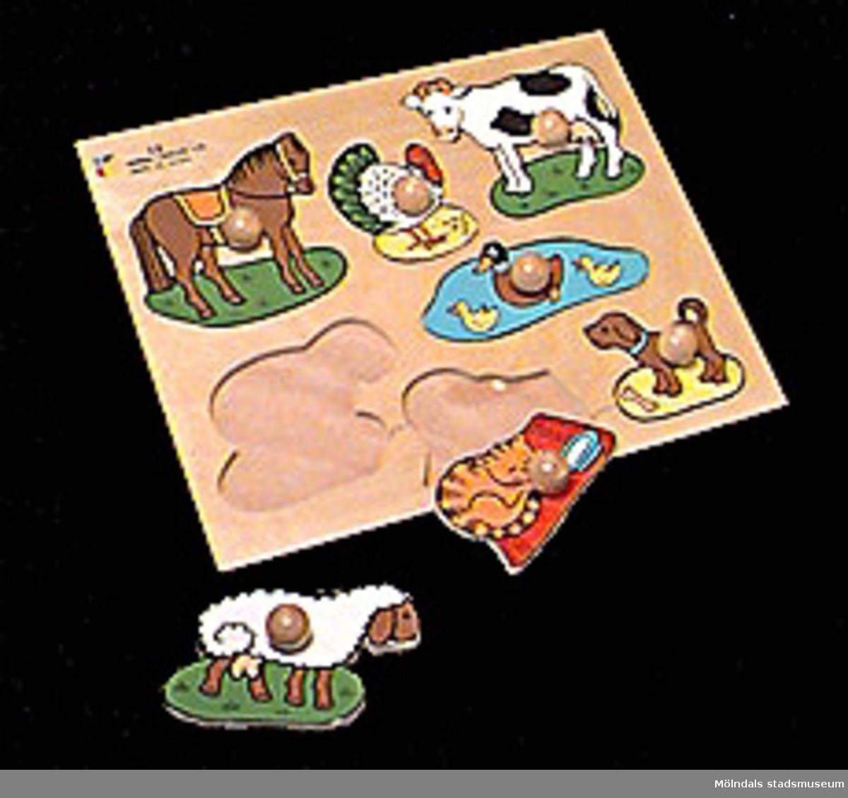 Läggspel (ett slags pussel) av kryssfanér i form av en rektangulär bricka med sju figursågade bitar i form av olika husdjur. Djuren kan, medelst påsatta små knoppar, lyftas ur och läggas tillbaka på sina platser på brickan. Pedagogiskt material för förskola och daghem. Märkt i röd tusch: KATRINEBERGS DAGHEM. Katrinebergs daghem var ett kollektivt daghem.Gåvan förmedlad genom Birgitta Bilting.