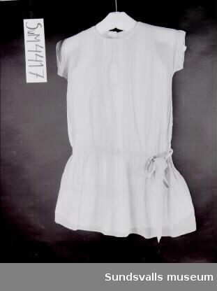 Klänning sydd i två lager. Den undre är vit och ärmlös med kort sprund i ryggen och volang med vit brodyr. Den övre är ljusblå med korta ärmar och lågt skuren midja med band knutet i rosett. Kjolen är rynkad. Stråveck på axlar, framstycke och kjol. Rund urringning med knypplad spets och sprund bak med vita knappar. Spetsinfällning fram. Vidhängande lapp med texten 'Bünsows samling'.