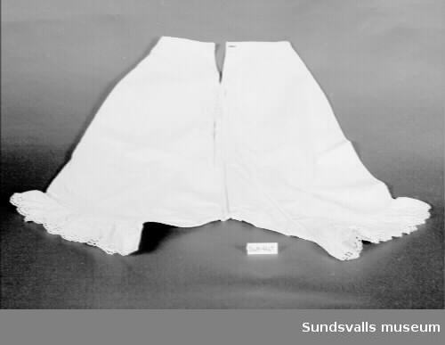 Vita benkläder i bomull. Midja med smal linning, sprund bak med två knapphål och tygklädda knappar. Vida ben med veck och rynkad brodyrspets. Tät langettsöm.