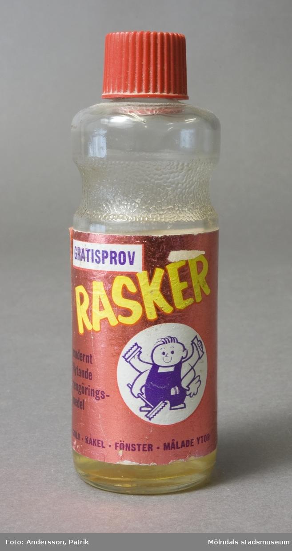 """Glasflaska med skruvkork. Påklistrad etikett med texten; """"Gratisprov - Rasker - modernt flytande rengöringsmedel"""". Bruksanvisning och tips står även på etikettens baksida. En del av innehållet är kvar i flaskan."""