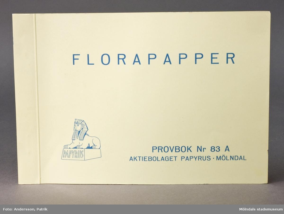 """Häfte med prover """"Florapapper Nr. 83A"""". Logotyp med sfinx på fundament. Pärm av ljusgrönt, glättat papper med blått tryck. Produktinformation på första sidan. Proverna i boken är märkta med siffra. Litteratur: Papyrus 1895-1945, Minnesskrift, Esseltes Göteborgsindustrier AB, Göteborg 1945."""