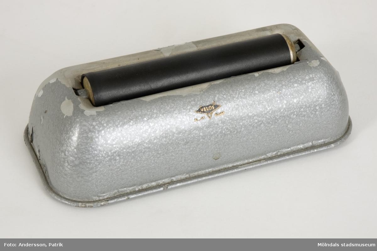 """Tryckcylinder, så kallad offsetcylinder, som använts vid papperstillverkningen på Papyrus. I en behållare för vatten, finns två metallcylindrar, varav den ena är klädd i svart gummi. """"Offsettryck är en allmänt använd tryckteknik där den färgburna informationen är överförd från en tryckplåt till trycksakens material (normalt papper), via en gummiduksbeklädd cylinder ('offset', set off, vilket avser den indirekta tryckmetoden)."""" (Wikipedia)Metallen på behållaren är gråmålad, och till stora delar avskavd. Under finns fyra, små, röda gummifötter. På ena långsidan, litet företagsemblem: """"Velos Trademark""""."""