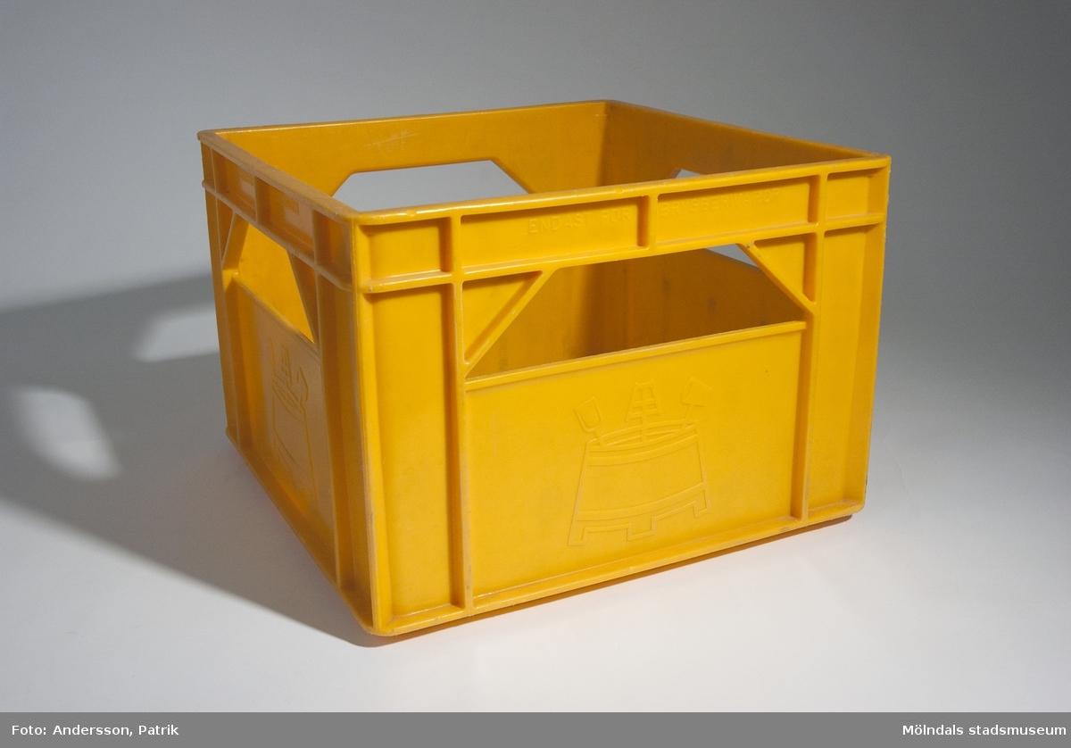 """Gul drickback från 1970-talet. På backens alla fyra sidor står """"BRYGGERIETS EGENDOM"""", plus en symbol ingjutet i plasten. Det finns också ett hål på varje sida som fungerar som handtag.Backen användes av givaren Kerstin Olofsson.I dessa backar var det vanligt att man förvarade sina LP-skivor.MåttLängd: 357 mm, Bredd: 357 mm, Höjd: 248 mm"""