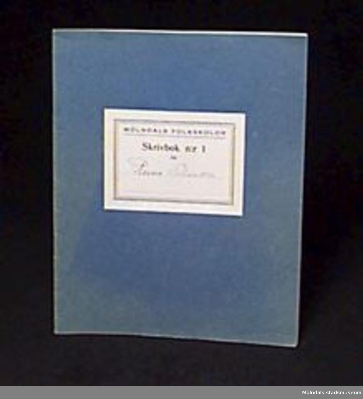 """Blå skrivbok med linjerade sidor. På omslaget en etikett med """"MÖLNDALS FOLKSKOLOR/Skrivbok n:r 1 för"""" samt skrivet med bläck: """"Rune Olsson"""". Använd för övning i välskrivning.Givaren gick hela sin skoltid i Toltorpsskolan."""